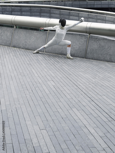 Female fencer lunging, outdoors
