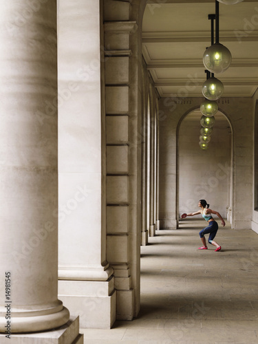 Female athlete throwing discus in portico, side view