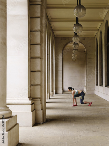 Female runner crouching in starting position in portico, side view
