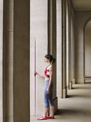 Female athlete holding javelin, standing in portico, side view