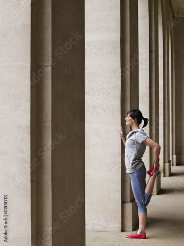 Woman stretching in portico, side view