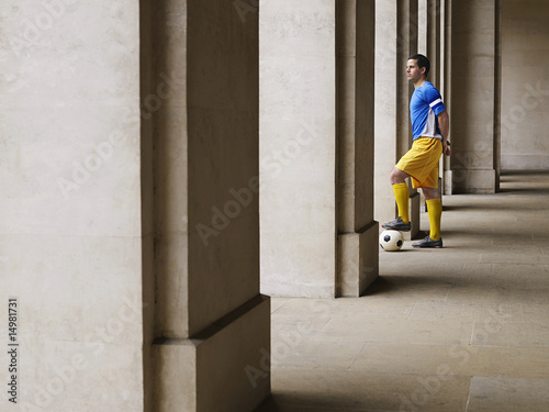 Soccer player holding foot on ball, standing in portico
