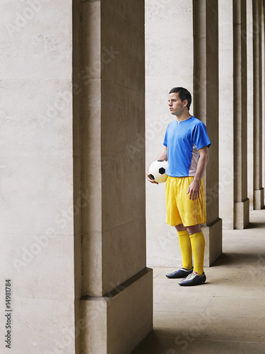 Soccer player holding ball, standing in portico
