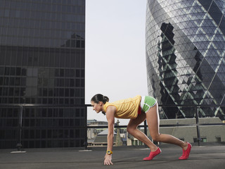 Woman crouching in starting position on downtown rooftop, side view, London, England