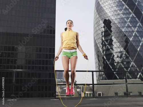 Woman skipping on skipping rope on downtown rooftop, low angle view, London, England