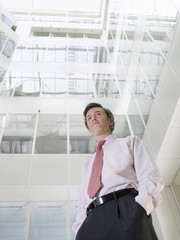 Business man standing in atrium of office building, low angle view