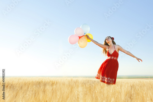young woman with colorful balloons relaxing in a wheat field