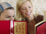 Two young women sitting on sofa, holding books, close up