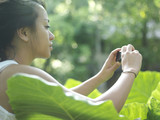 Young woman taking photograph of leaf, side view