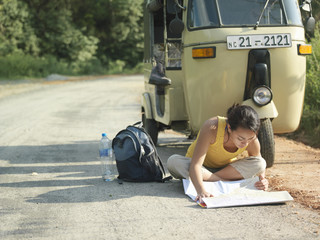 Young woman sitting on road reading map, motor scooter in background