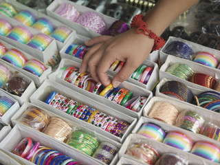 Young woman looking at different bracelettes on display, close-up on hand