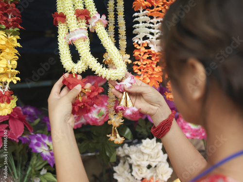 Young woman looking at artificial flowers necklaces, back view, selective focus