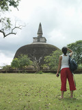 Young woman looking at stupa, back view