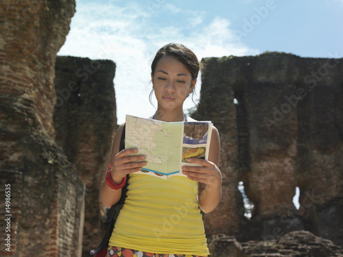 Young woman reading guide book, ancient ruins in background
