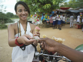 Young woman paying for ice cream at street market, smiling