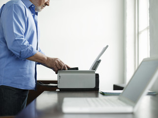 Middle-aged man using printer, side view, mid section
