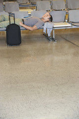 Traveller lying down on chairs in airport lobby