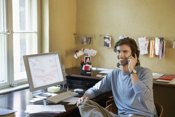 Young man using phone in office