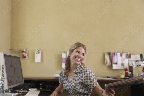 Woman handing off papers in office