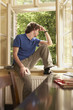 Young man sitting on sill looking out living room window