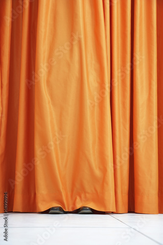 Person hiding behind orange curtain