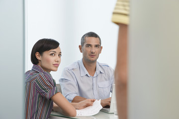 Two workers looking up at co-worker mid section standing in office doorway
