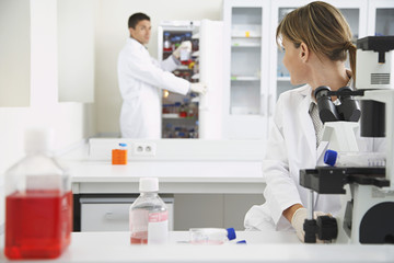 Scientist using microscope with second scientist getting specimen in laboratory