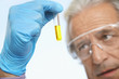 Scientist examining test tube of yellow liquid, close-up, focus on hand