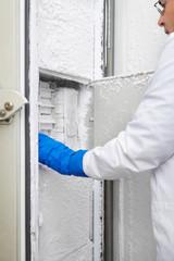 Scientist reaching into freezer in laboratory