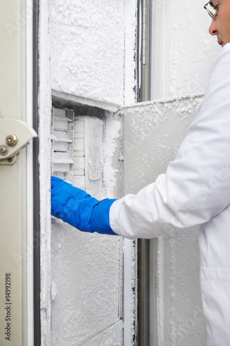 Scientist reaching into freezer in laboratory