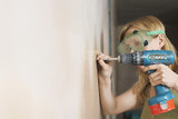 Woman wearing protective goggles drilling wall, close-up