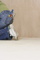 Woman with paintbrush and hand tools in back jeans pocket kneeling on floor, low section