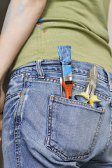 Woman with paintbrush and hand tools in back jeans pocket,  mid section, close-up