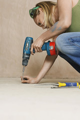 Woman drilling floor, close-up
