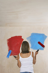 Woman facing wall painted on ble and red, holding with paint rollers, back view