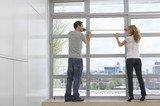 Rear view of young couple measuring window in modern apartment