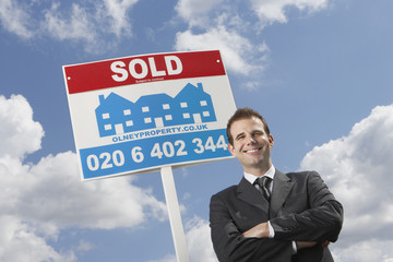 Real estate agent in front of sold sign, against cloudy sky