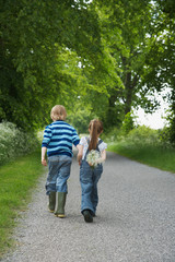 Boy and girl 5-6, 7-9 walking on country lane