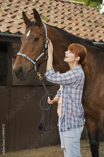 Woman with horse outside stable
