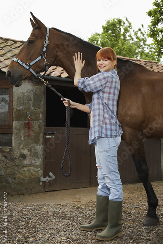 Woman with horse outside stable, portrait