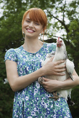 Woman holding hen in garden, portrait
