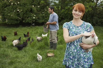 Couple feeding hens in garden, portrait
