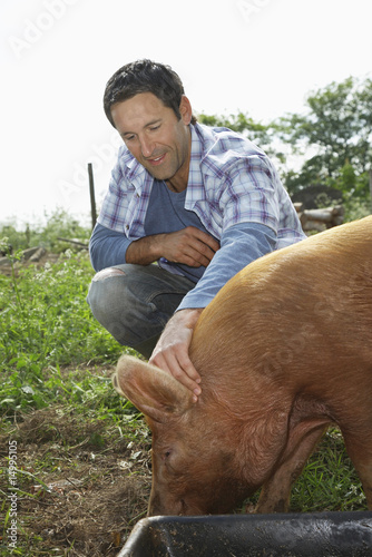 Man holding pig in sty