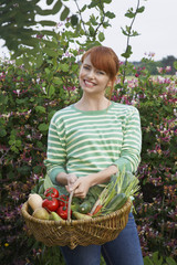Woman holding fruit and vegetable basket in garden, portrait