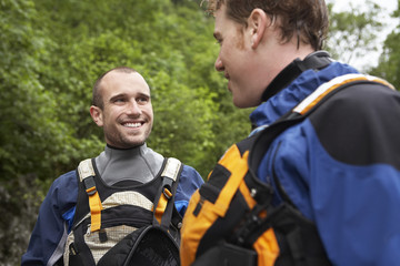 Two men wearing wetsuits, outdoors