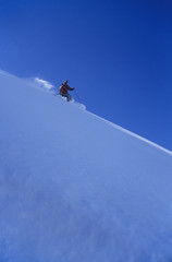 Person skiing down slope, side view