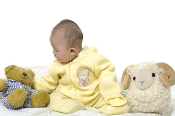 Baby with bear toys and sheep