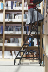 Office worker standing on ladder in file storage room, low section
