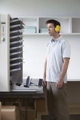 Man wearing headphones standing by photocopier