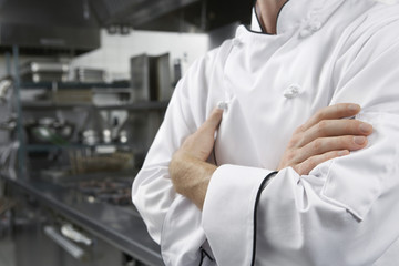 Male chef with arms crossed in kitchen, mid section